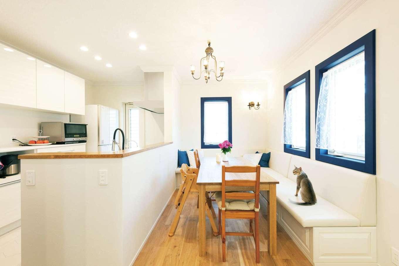 F.Bird HOUSE(袴田工務店)【輸入住宅、間取り、ガレージ】リビングとダイニングはルーバー付きの引き戸で間仕切りできる。L字型のソファは作り付け。青い窓枠がとってもおしゃれ