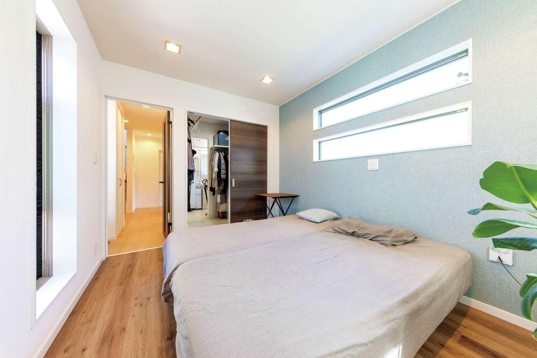 明和住宅【狭小住宅、間取り、屋上バルコニー】寝室は暗めの色で統一してシックに。向かって左側の通路のほかに、右側のウォークインクローゼットから直接洗濯部屋に抜ける動線も確保した