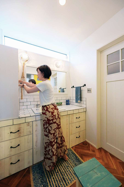 洗面はキッチンとコーディネートしたサブウェイタイルで造作。一つ一つの小物や照明も吟味した