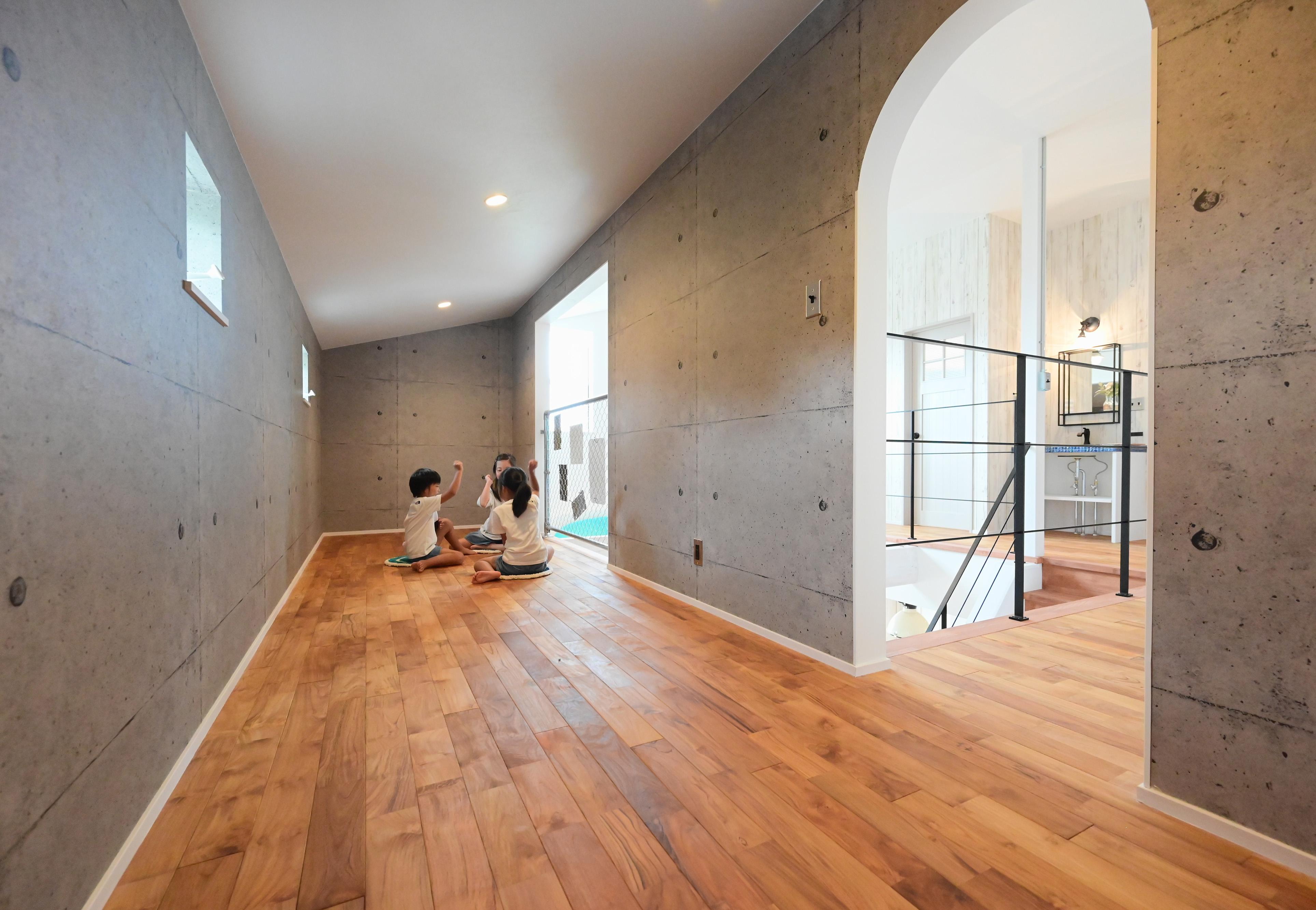 クローバーハウス 【輸入住宅、省エネ、インテリア】2階に設けたフリースペースは、RC調のクロスを設え、遊び心満載。三姉妹の遊び場としても収納庫としても機能する