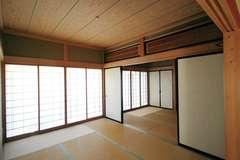 愛着のある欄間を活かして明かり取りに。塗り壁は調湿・消臭効果に優れたシラス壁、天井にも無垢板を採用。緑の借景を楽しみながら、ゆったりとくつろげる和室は、家族にとって自慢の一室となった。
