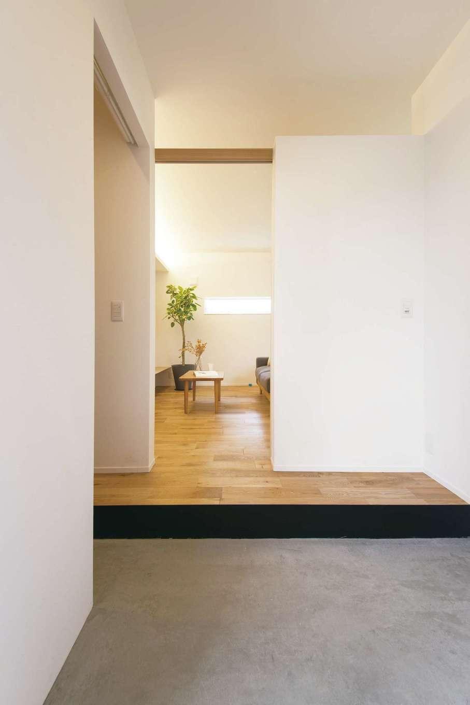 ARRCH アーチ【狭小住宅、建築家、平屋】玄関とLDKの境の壁は上部をオープンにしてあり、LDKの灯りが玄関にもこぼれてくる。左手の奥はシューズクローク