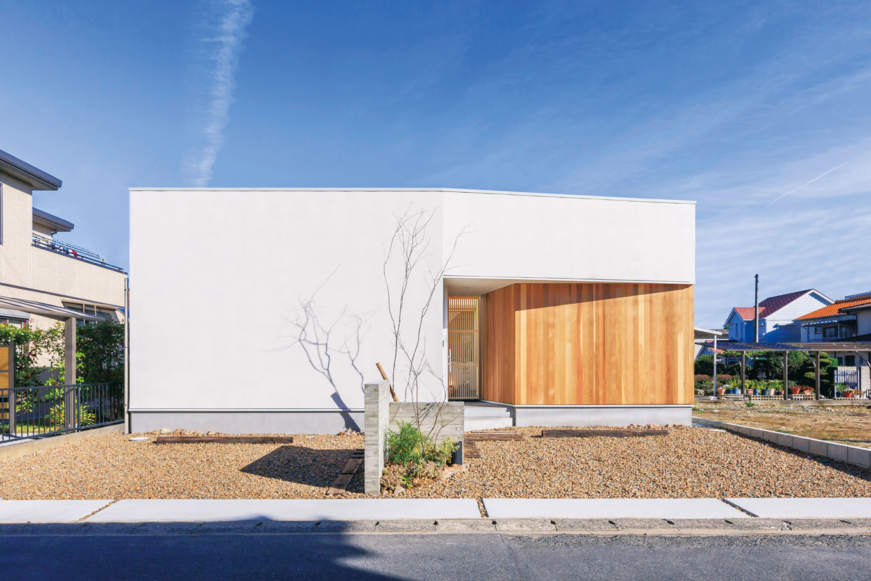 ARRCH アーチ【狭小住宅、建築家、平屋】55坪の敷地に4台分の駐車スペースを確保し、延床26坪の平屋を実現。外観デザインはシンプルな白い箱型で、板張りの壁が美しく映える。プライバシーに配慮し、道路側には窓を設けていない