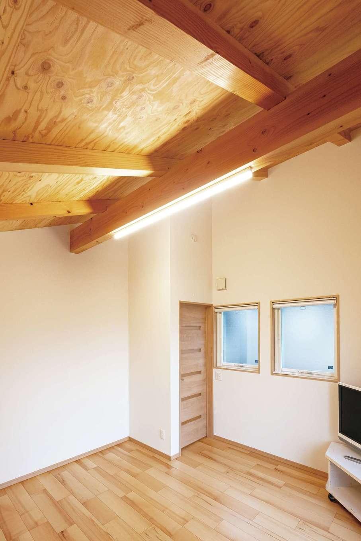 板張りにした勾配天井の寝室。朝起きると木目がパッと目に入り山小屋にいるような感覚に。クローゼットがないため広々と使えるのもうれしい