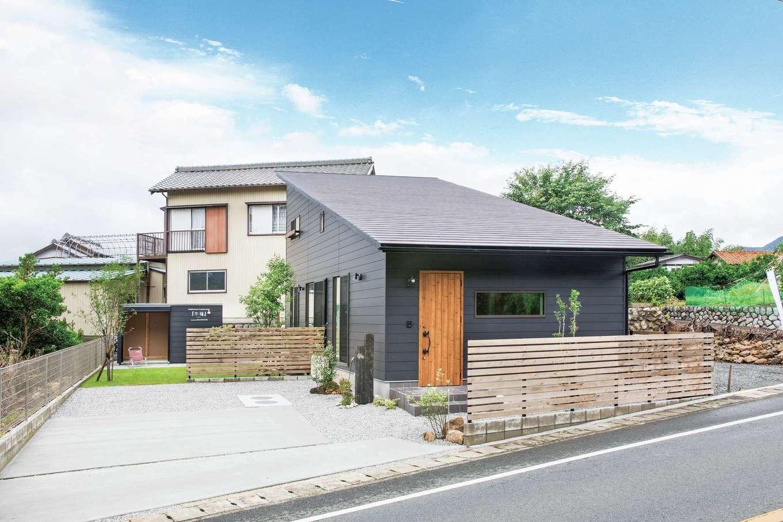 住たくeco工房【1000万円台、子育て、自然素材】黒いガルバリウムの外壁に大屋根が印象的な1.5階建ての外観。ウッドフェンスや植栽、物置の位置を含め外構もトータルで提案してくれるところも魅力