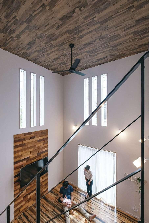 アフターホーム【趣味、屋上バルコニー、ガレージ】無垢床、木目調の天井、壁の木製パネルとウッディな質感で統一したぬくもりのある空間。外観のアクセントにもなるスリット窓は外からの視線を遮るフィルムを採用。大空間でも断熱性が高く、エアコン一つで快適に過ごせているそうだ