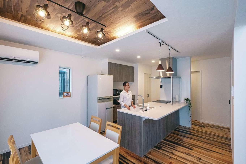 アフターホーム【趣味、屋上バルコニー、ガレージ】ペニンシュラ型のフラットキッチンは壁の向こう側を通って回遊できる仕様。ダイニングの上は間接照明付きの折り上げ天井に