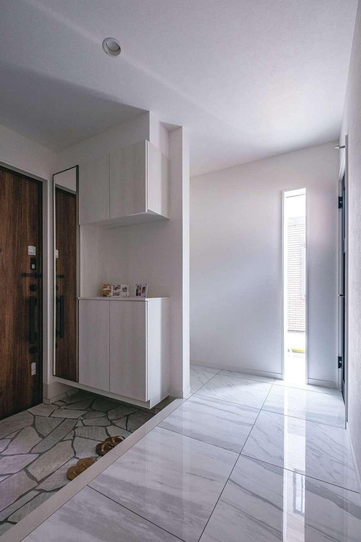 アフターホーム【趣味、屋上バルコニー、ガレージ】白でまとめた玄関はリゾートホテルのような仕上がり。スリット窓から光を取り入れて明るさも確保した