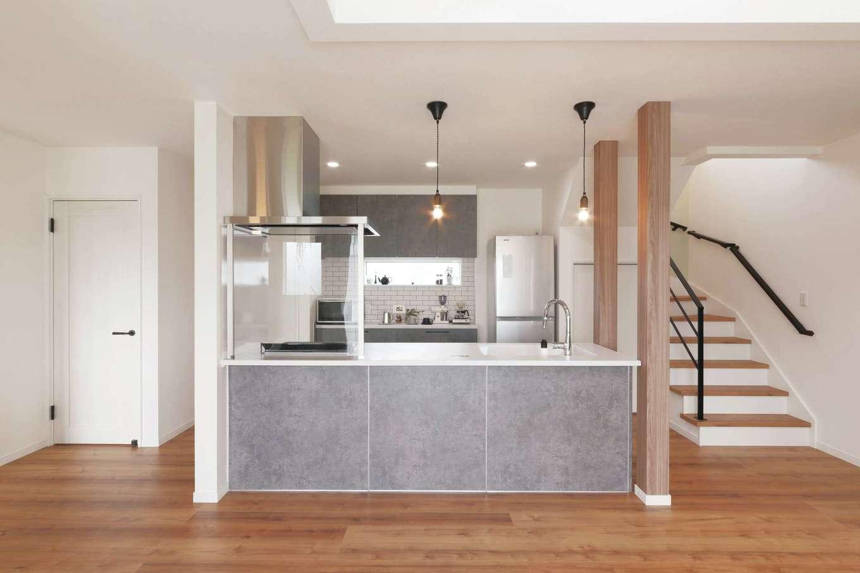 アフターホーム【デザイン住宅、趣味、間取り】使いやすい動線も重視して配したアイランドキッチン。グレーの面材は奥さまが「どうしてもこの素材で」と選んだ特注品。料理しながらリビングダイニングが見えるガラスの油よけや、タッチセンサー付きの蛇口にもこだわりを