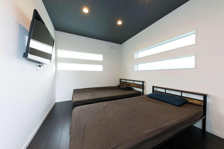 スリット窓がおしゃれな寝室。テレビは壁に取り付けてすっきりと