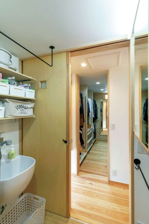 あだちの家。足立建築【収納力、間取り、インテリア】洗面室の多目的シンクはつけおき洗いに利用。上部のアイアン製のバーはタオル干し。締め切れば乾燥機もかけられる。奥に見えるファミリークローゼットは将来も見越して1階に配置。将来的に下階だけで生活できるように設計上も配慮済み