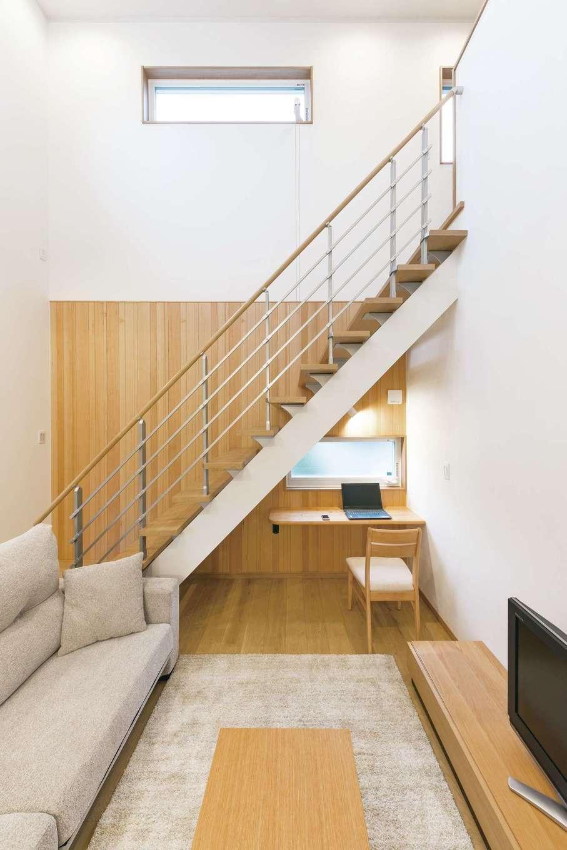 吹抜けのリビング。木のアクセントウォールが温もりを添える。階段下のデッドスペースを活かして、長男のスタディコーナーを設置。プライバシーと明るさを両立させるため、窓の位置と大きさまで考慮した