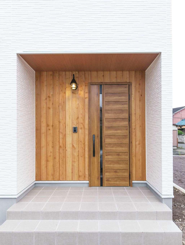 長野県産のカラマツに水を弾く特殊塗料を施した玄関ポーチ。木の温もりあふれる深い軒は、雨の日のストレスも軽減してくれる