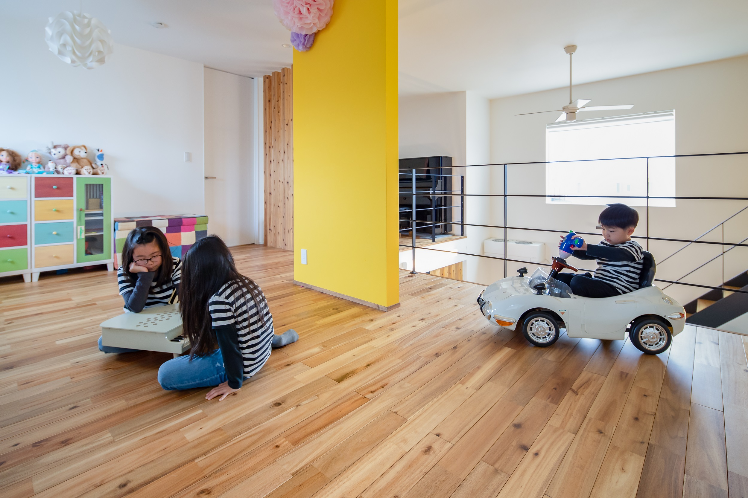 S.CONNECT(エスコネクト)【デザイン住宅、子育て、建築家】2階のフリースペースで元気いっぱいに遊ぶ子どもたち。イエローのアクセントウォールは目隠しにちょうどいい位置にあり、圧迫感がないサイズが絶妙。無垢の床の温もりが素足にやさしく、座り込んだり、寝転がって遊んだりしても気持ちいい