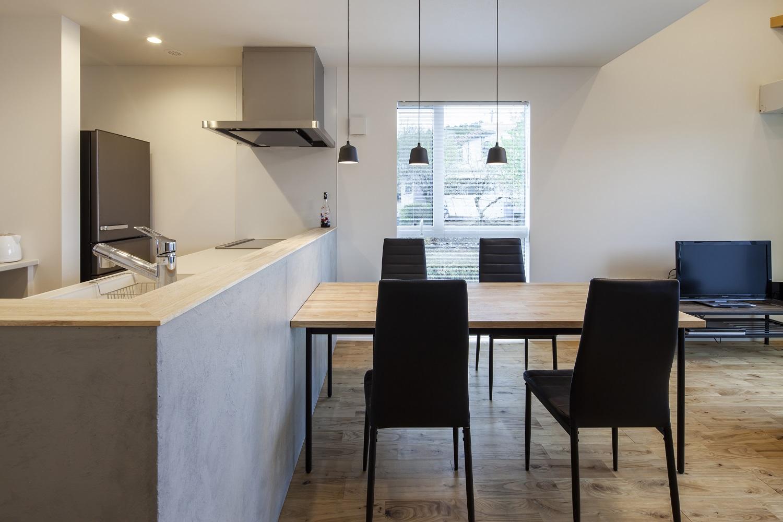 S.CONNECT(エスコネクト)【デザイン住宅、狭小住宅、建築家】景色を眺めながら楽しく料理できるモルタル仕上げのオープンキッチン。シンプルで上質なペンダントライトのチョイスにも施主さんのセンスが光る