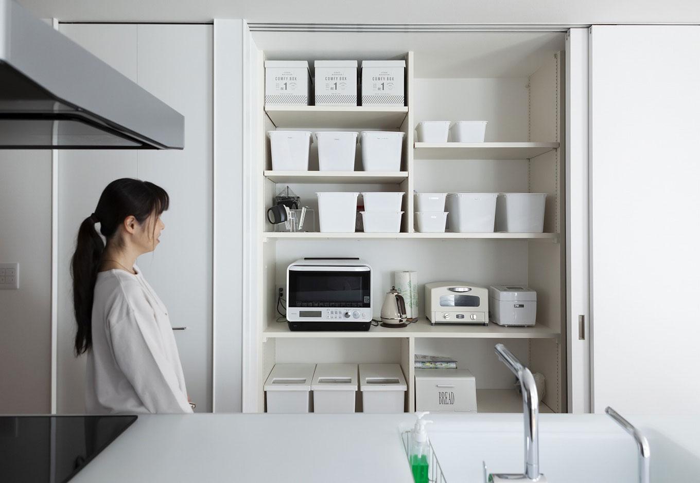 キッチンの背面に設けた収納スペースは奥さまのこだわりで収納ボックスや家電もすべて白で統一。大きな扉で生活感を隠しておくこともできる