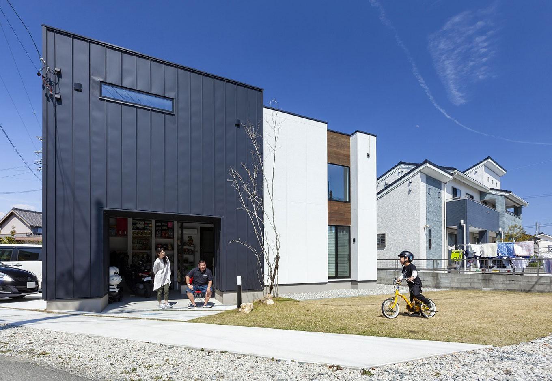 紺と白の建物が2棟隣接しているかのように、趣向の異なる2つのデザインのコンビネーションが絶妙な外観。バイクのインナーガレージも間口を広くとってあり、開放的な印象