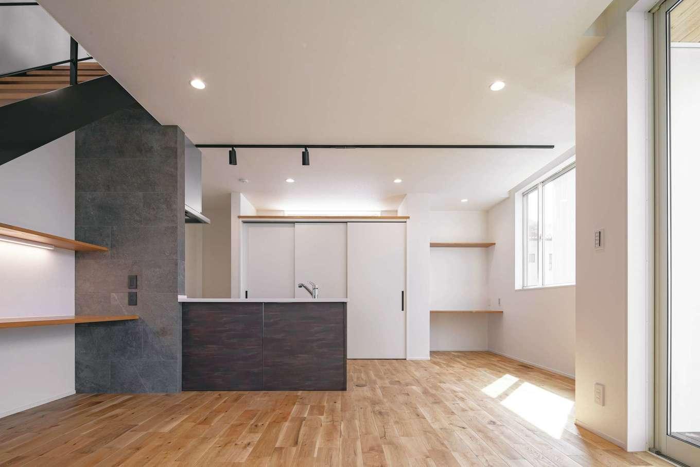 キッチンのパネルは、オーク材の床の色、質感に合わせて奥さまが選んだ。不意の来客時にサッと食器棚や調理家電を隠せるよう、バックヤードに引き戸を採用した