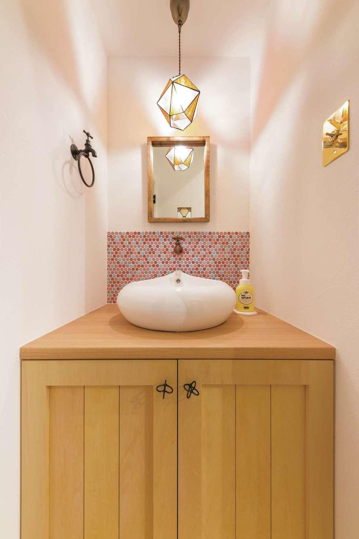 おしゃれなボウル、タイル、鏡、照明、取っ手がバランス良く調和したゲスト用の手洗いコーナー