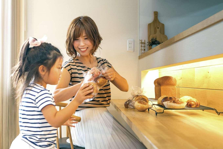 五朋建設【間取り、デザイン住宅、高級住宅】ダイニングカウンターは焼いたパンの仕分けや包装に便利。お子さまの勉強用に設けたスポットを照らしてパンを撮影し、インスタにアップ
