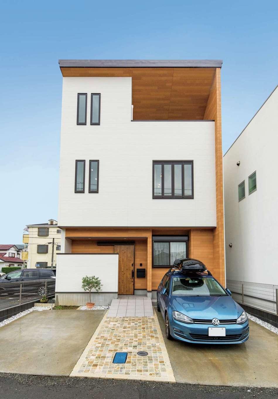 五朋建設【間取り、デザイン住宅、高級住宅】3階建ての外観。富士山ビューと風通しを意識しつつ、窓をバランス良く配置。ファサードの美観を保つため、玄関ポーチの白い壁の後ろに自転車置き場を確保