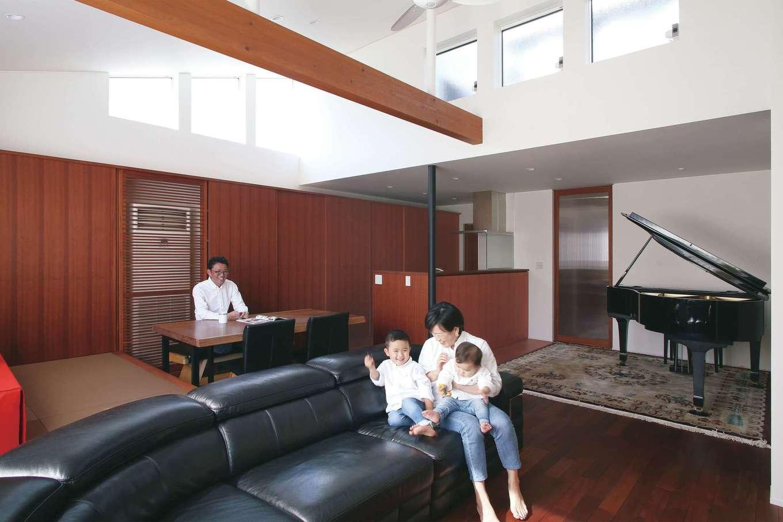 神谷綜合建設 カミヤの家【デザイン住宅、収納力、二世帯住宅】高さのある勾配天井と高窓により、開放感と明るさは抜群。グランドピアノを置いても広々。サペリの落ち着いた色合いも相まって、重厚感ある空間に仕上がった。