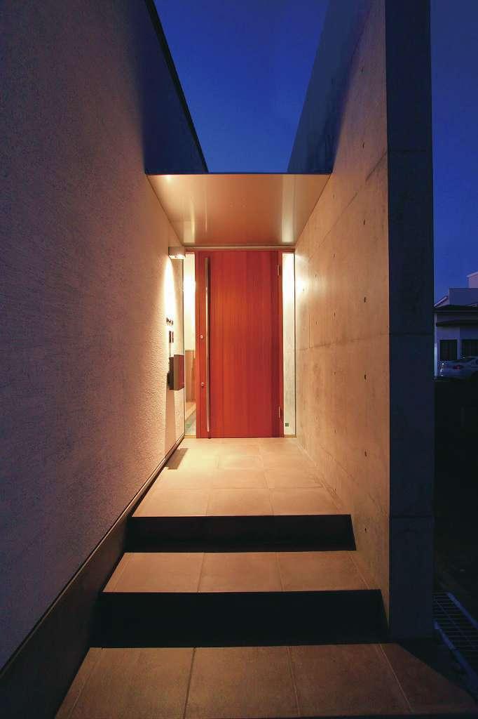 神谷綜合建設 カミヤの家【デザイン住宅、収納力、二世帯住宅】赤褐色のサぺリを使った製作建具とコンクリート壁の玄関は、まるで小さな美術館のエントランスのよう