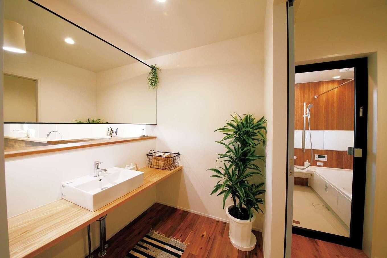 大きな鏡と木目調の浴室でホテルライクに仕上げられた水回りのプラン例。キッチンから近く、家事のしやすさにも配慮が行き届く
