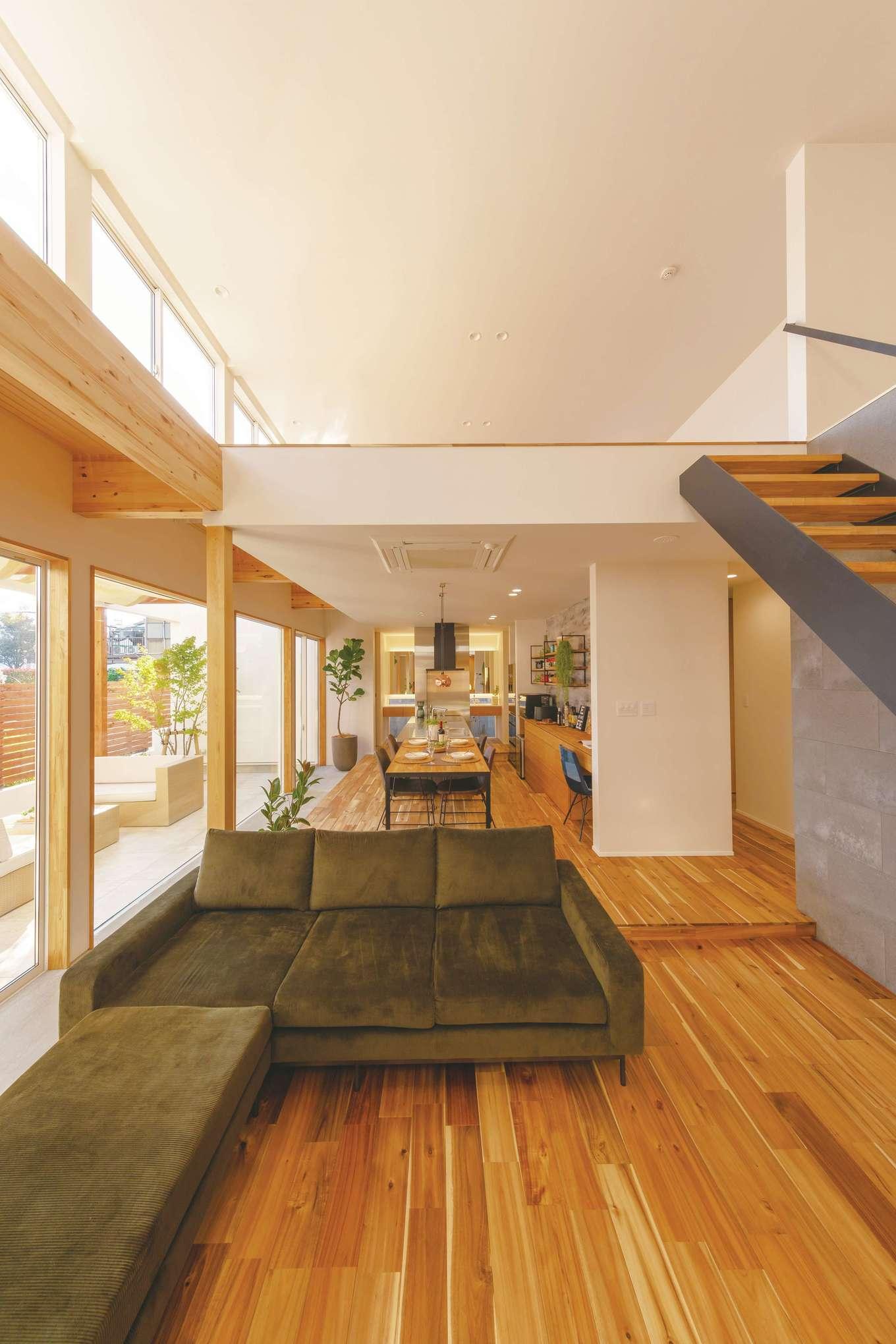 住家 ~JYU-KA~【デザイン住宅、間取り、建築家】リビングは大きな吹き抜けに。ダイニングと段差を設けることで、空間を緩やかに仕切る。2階は壁も手すりもない、フラットで大きなロフト。抜群の開放感はまさしくアウトドア感覚だ
