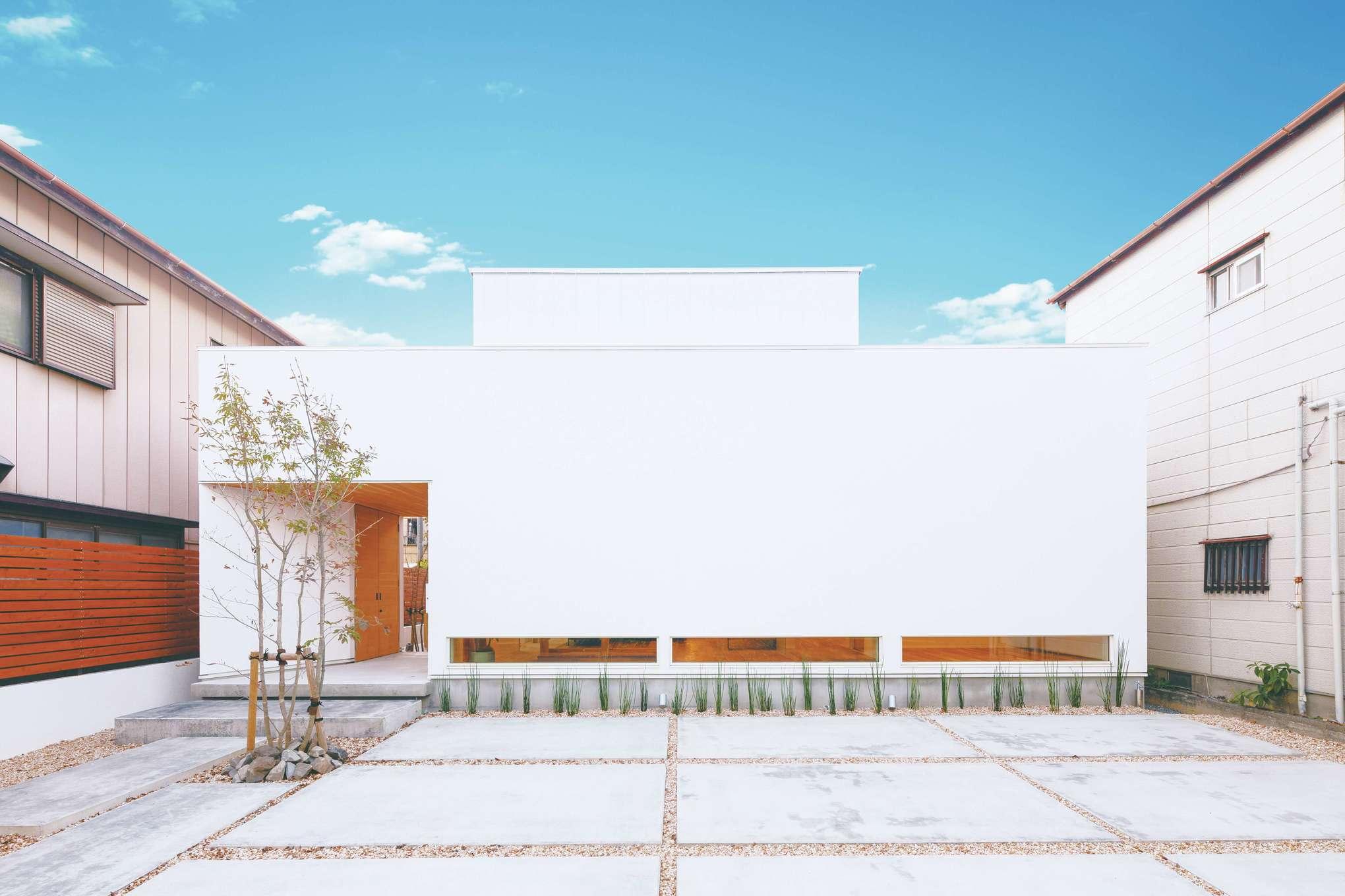 住家 ~JYU-KA~【デザイン住宅、間取り、建築家】開口部を極力減らした、シンプルを極めたファサード。ポーチを抜けた先はテラスへと続く