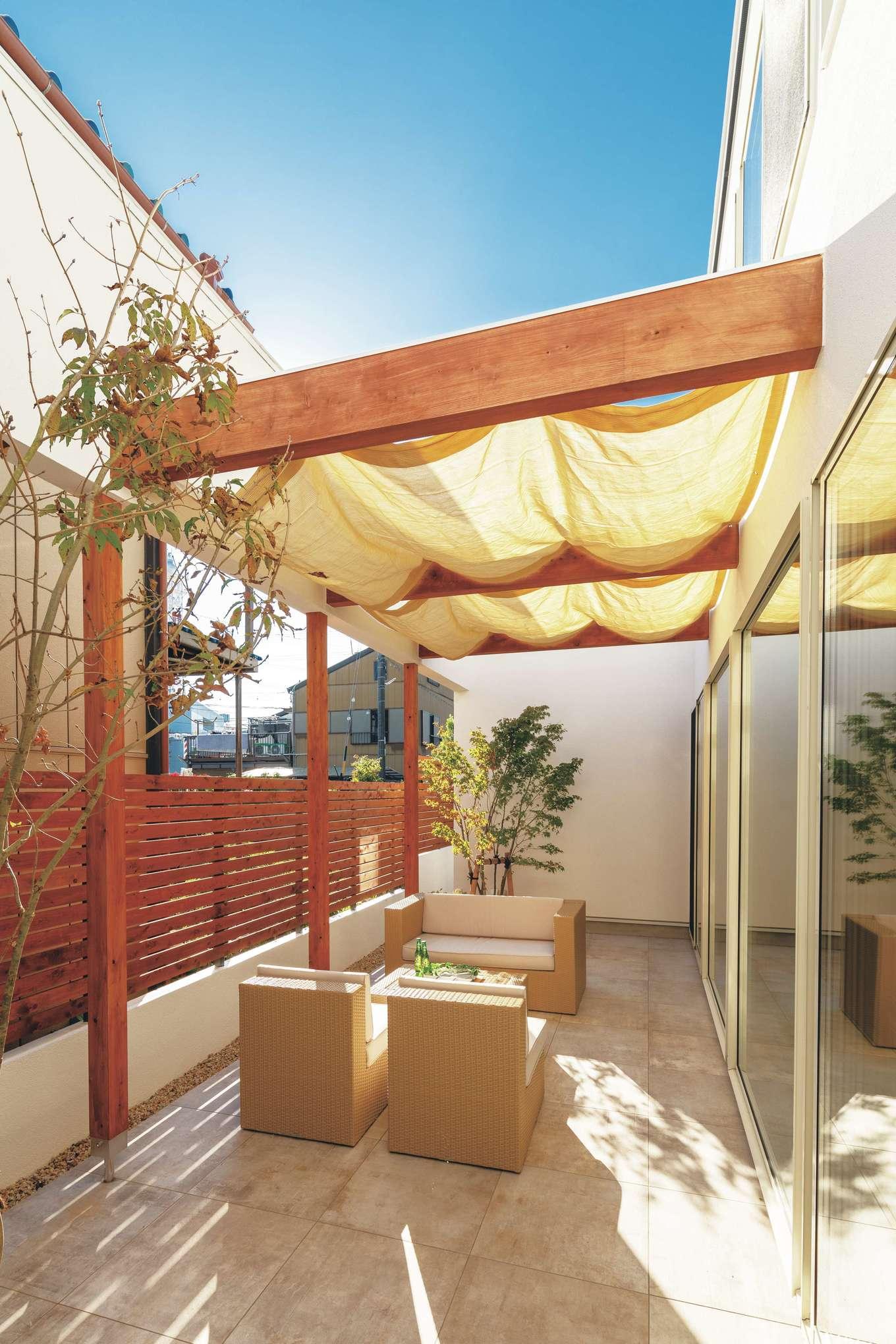 住家 ~JYU-KA~【デザイン住宅、間取り、建築家】家と外を繋ぐテラス。日常の中で自然を感じるスペース。可動式のシェードを取り付け、夏の日よけ対策も万全。子どもたちを安心して遊ばせることができる