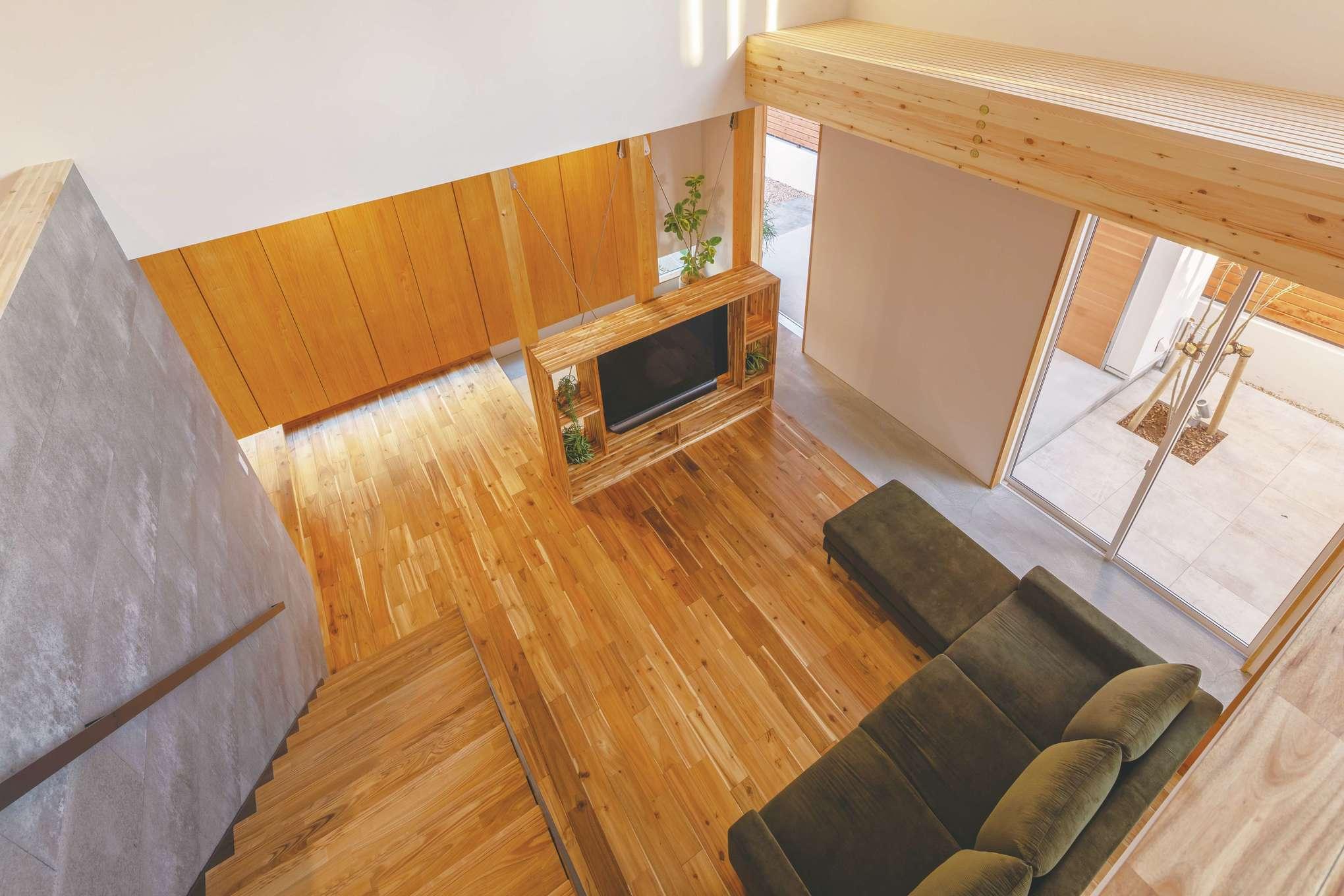 住家 ~JYU-KA~【デザイン住宅、間取り、建築家】家の中で外の感覚になれる場所が、玄関からリビング、ダイニングまで延びる土間だ。生活スペースを取り囲むこの空間が、家の中と外の境界を柔らかくぼかし、中と外の繋がりをいっそう強めている。土間部分の天井は格子状になっているので、2階からの自然光が、まるで木漏れ日のように優しく降り注ぐ。