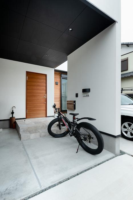 住家 ~JYU-KA~【デザイン住宅、屋上バルコニー、建築家】木目調の玄関ドアが真っ白な外観のアクセントに。駐輪スペースも広々確保