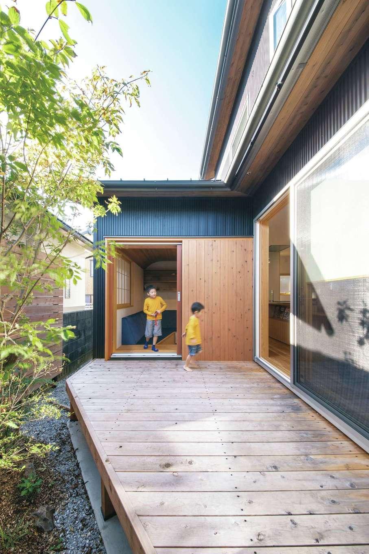 ぴたはうす 安食建設【自然素材、省エネ、間取り】隣家が平屋のため、建物をコの字型に配置して中庭から光と風を取り込むように工夫した。外と内をつなぐウッドデッキはアウターリビングとして大活躍