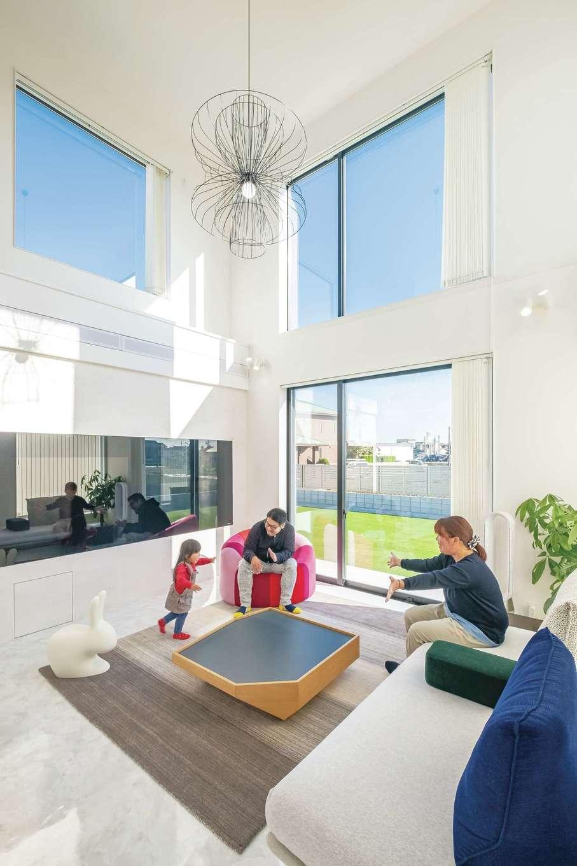 デザインハウス【デザイン住宅、子育て、間取り】吹き抜け部分にも大きなフィックス窓を配し、自然光が明るく降り注ぐリビング。白を基調にした室内だからこそ、インテリアの彩りや庭のグリーンカラーがよく映える