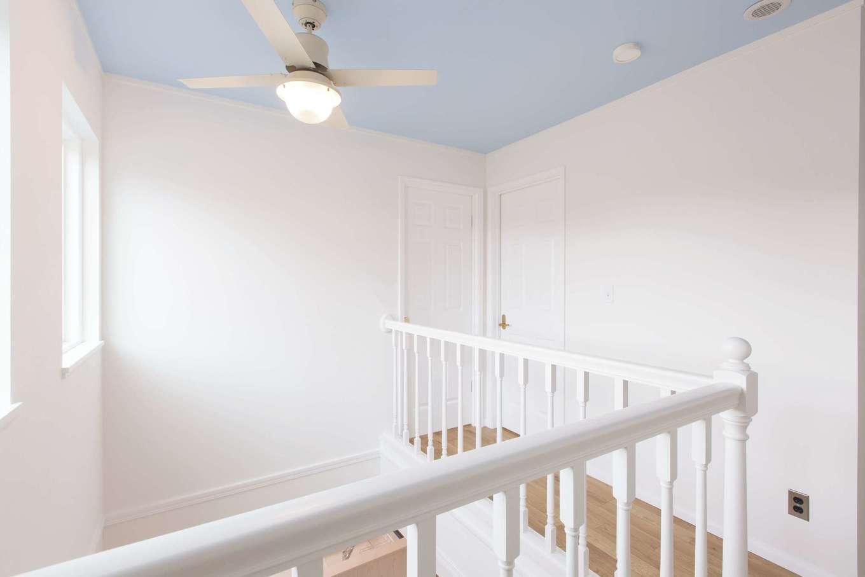 セルコホーム浜松(オバタケイ)【輸入住宅、趣味、インテリア】2階のホール。壁に合わせて、シーリングファンや手すりも白で統一。水色の天井は青空のイメージ