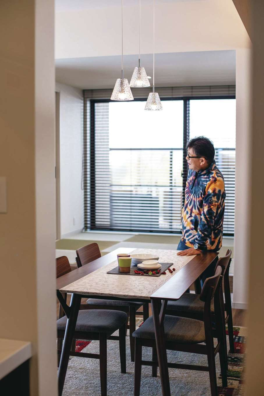 Um House(マル祐戸田建築)【夫婦で暮らす、間取り、平屋】ガラスのペンダントライトがおしゃれなダイニング。仏間もある小上がりの畳コーナーは、来客時にベンチ代わりにもなる。空間のテイストに合わせて、木製ブラインドでコーディネート