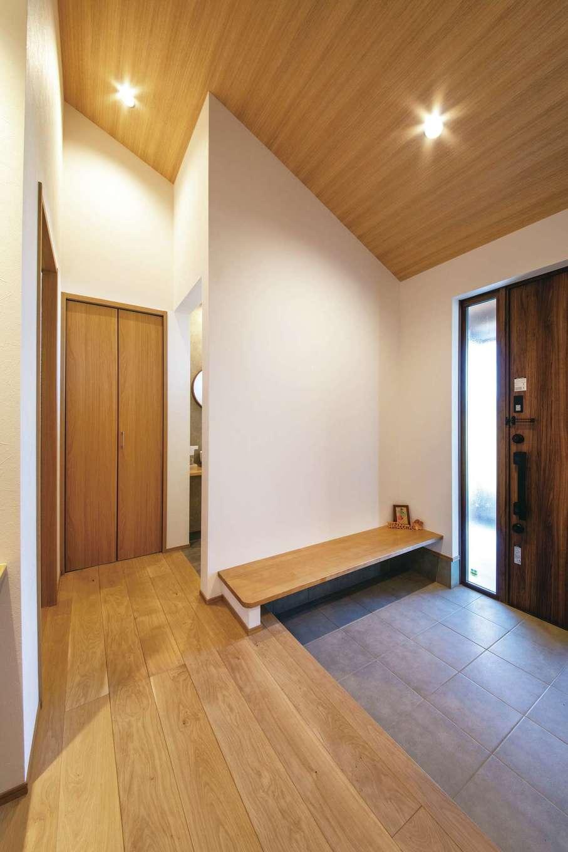 コットンハウス【子育て、二世帯住宅、省エネ】勾配天井でより広く感じる二世帯共有の玄関ホール。木のベンチは両親にも子どもたちにもやさしくて便利