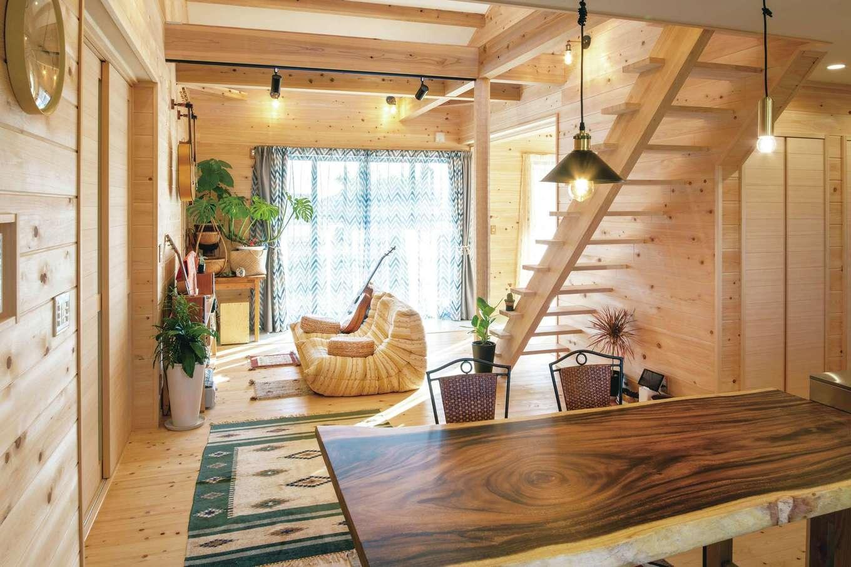 ひのきの家 静岡県家づくり浜松協同組合【趣味、自然素材、省エネ】モンキーポッドの造作ダイニングテーブルが趣深い。ログハウスを思わせる内装に照明が映える