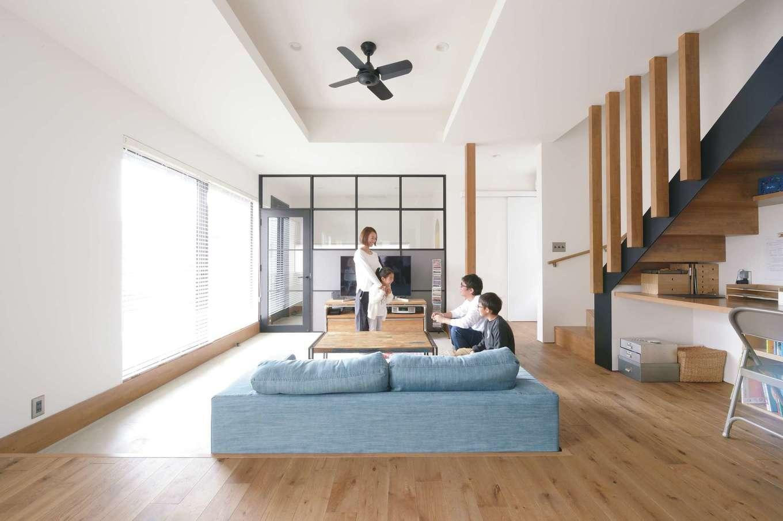 """MABUCHI【デザイン住宅、狭小住宅、建築家】モルタル仕上げの土間玄関からそのままフラットにつながるピットリビング。""""おこもり""""感があるので、家族みんなが自然に集まってくる。ダイニングキッチンからフロアダウンさせたことで、空間に変化が生まれた。吹抜けの代わりに折り上げ天井を採用し、その上が小上がりの畳コーナー。アイアンに見える黒いフレームの間仕切りがシンプルな空間を引き締めると同時に、ギャラリーのような佇まいを見せている"""