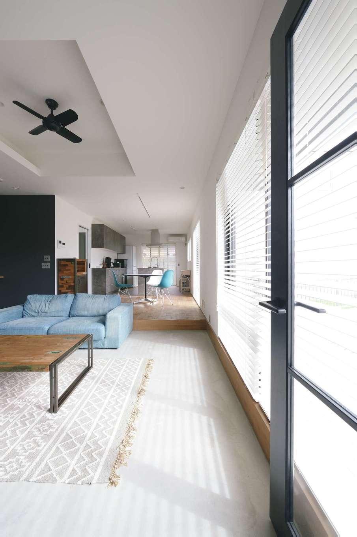 MABUCHI【デザイン住宅、狭小住宅、建築家】玄関ホールから連続するモルタルの土間リビングは、外国生活が長かったKさん家族にぴったり。段差を設け、ダイニング・キッチンと緩やかにゾーニングした