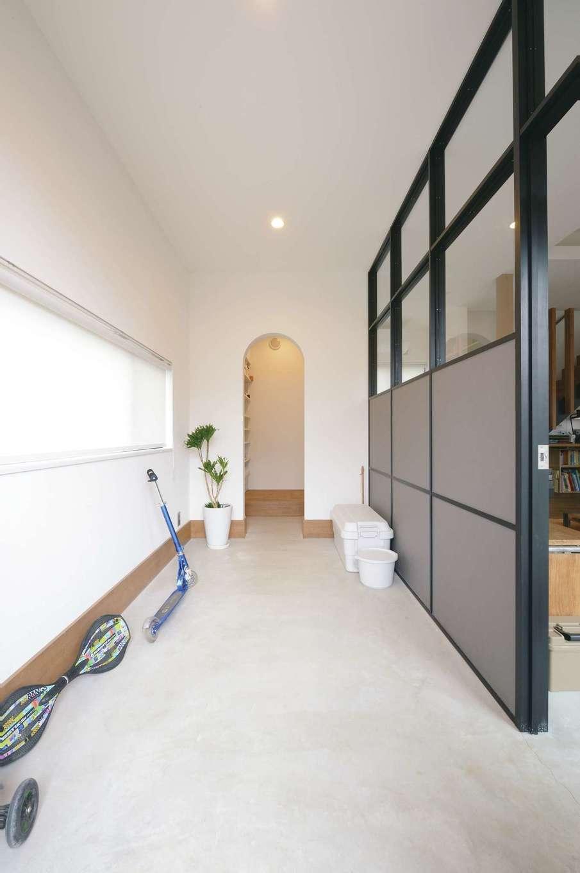 MABUCHI【デザイン住宅、狭小住宅、建築家】外国のアパルトマンを彷彿とさせる土間玄関。床はモルタル。間仕切りのフレームは木を黒く塗装してニュアンスを出した