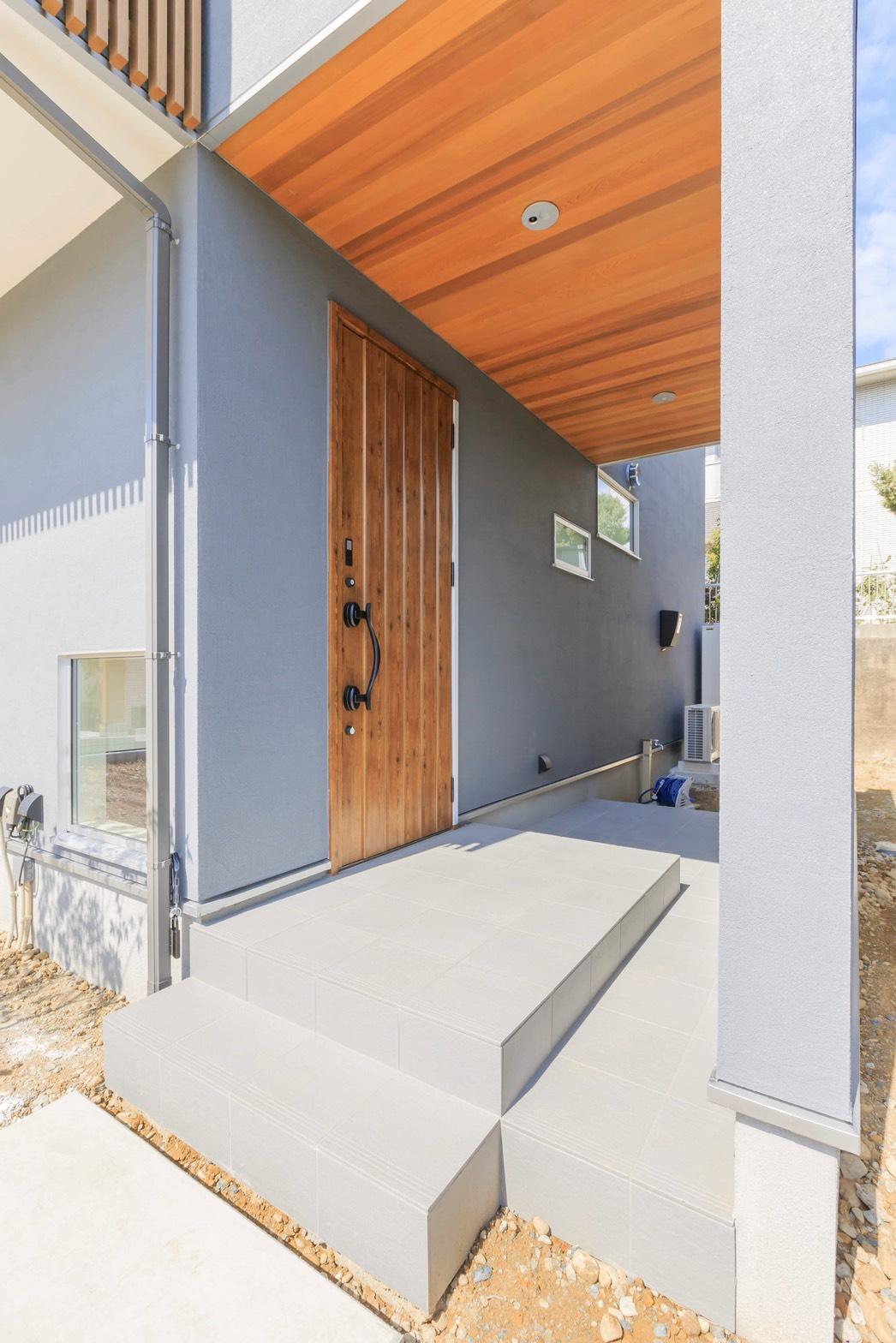 ARRCH アーチ【省エネ、間取り、建築家】レッドシダー張りの天井と木扉がグレーの塗り壁に映える玄関アプローチ