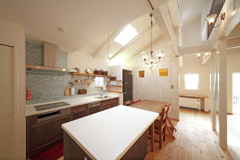 BLUEHOUSE(ブルーハウス)【子育て、収納力、自然素材】壁付のI型キッチンにアイランド型の作業台をプラス。奥さまがクッキングを存分に楽しめる。ときにはママ友を招いて一緒にお菓子作りを楽しむことも。勾配天井にはトップライトを設けて明るさを十分に確保