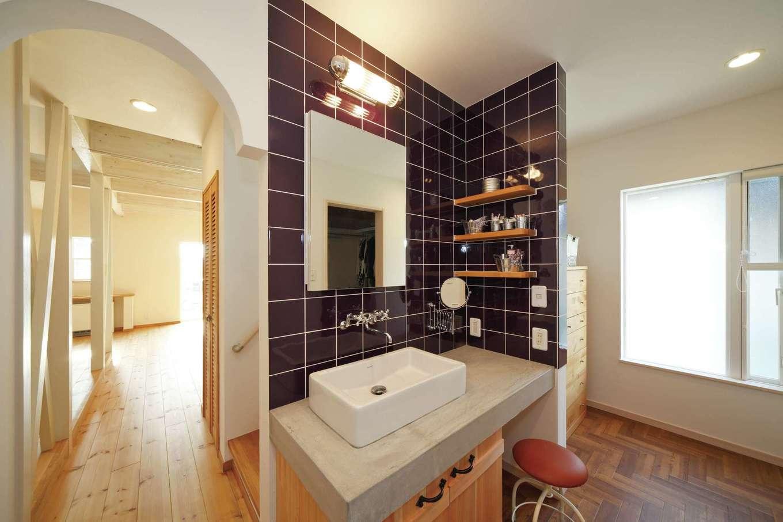 BLUEHOUSE(ブルーハウス)【子育て、収納力、自然素材】黒いタイルとモルタルのカウンターがスタイリッシュな洗面スペース。奥には旧宅で使っていたタンスを設置。洗面の背面にはファミリークローゼットがあり、洗う・干す・しまうという洗濯の動線を格段に短縮した