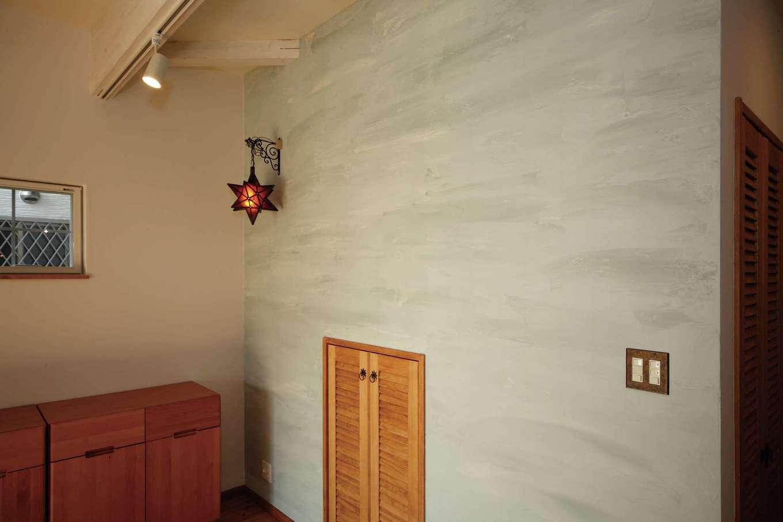 BLUEHOUSE(ブルーハウス)【子育て、収納力、自然素材】リビングのアクセントクロスや照明のコーディネートにこだわり、ご家族らしさを演出。スキップフロアの下部は収納に利用し、リビング側から使えるように扉を設けた