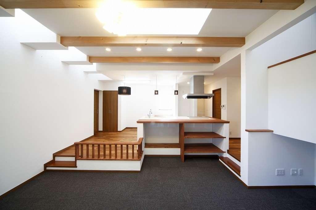 小さな平屋のスタイリッシュなリビング&キッチン、愛犬のしつけも兼ねて段差を設けています