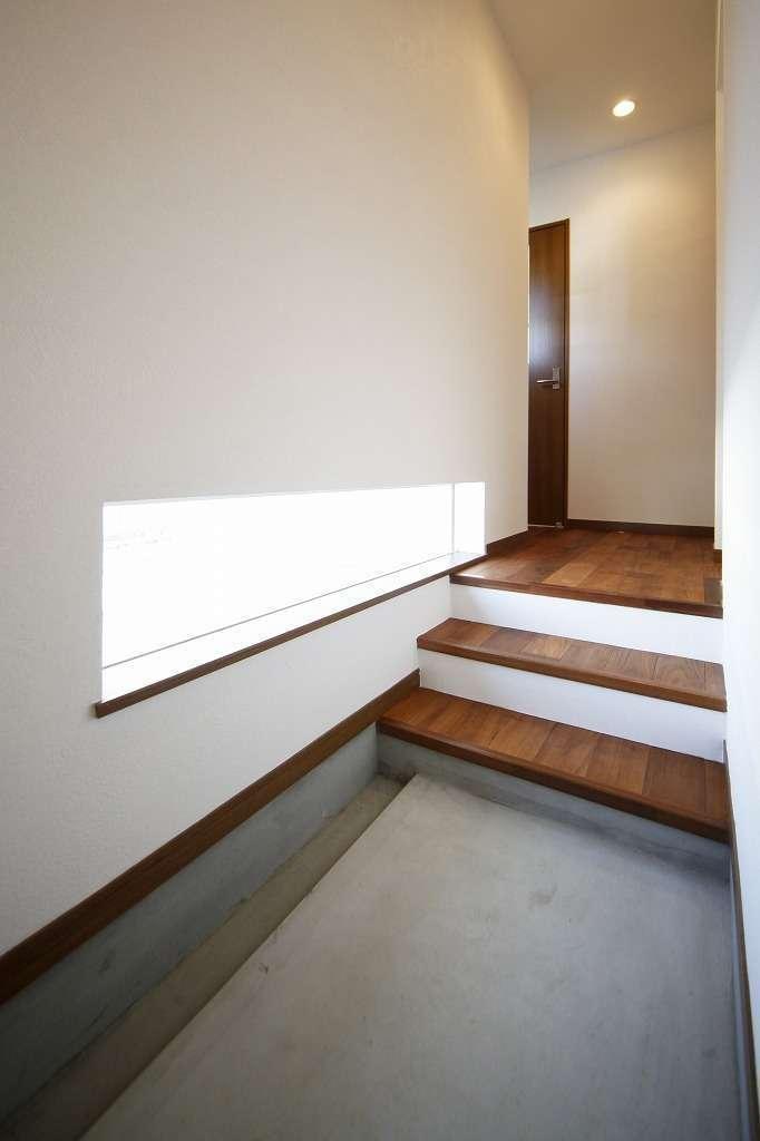 BLUEHOUSE(ブルーハウス)【狭小住宅、ペット、平屋】プライバシーに配慮して窓を低めに設けた玄関土間。玄関の外に階段を設けると駐車場スペースが狭くなるため、室内に設けてある