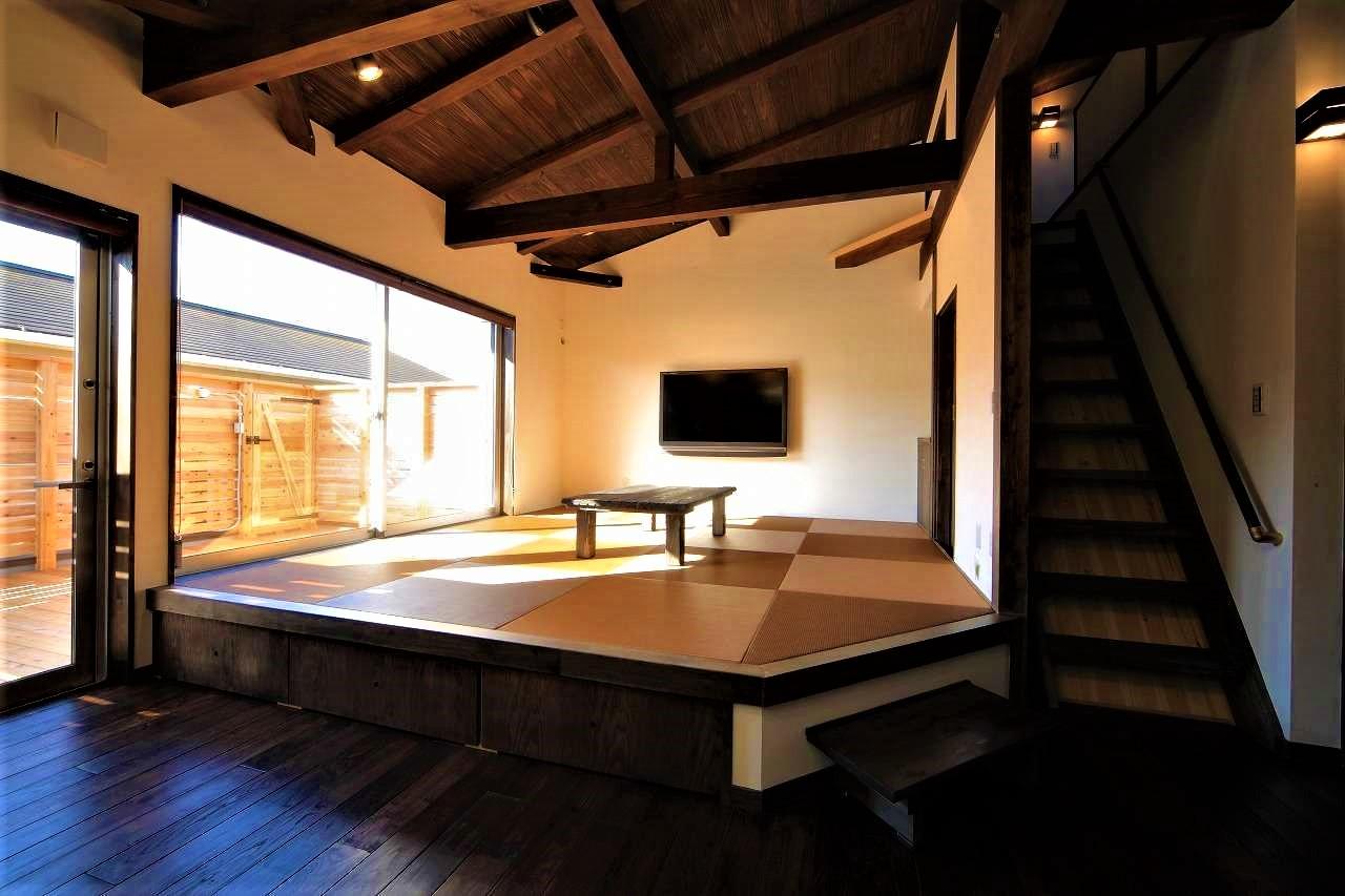 BLUEHOUSE(ブルーハウス)【和風、屋上バルコニー、建築家】LDKは木部を濃い色調に統一し、古民家風の安らぎ空間を演出。リビングダイニングは小上がりの畳敷きにして、自由な格好でのんびりくつろげる空間に。南面には板張りのベランダが広がる
