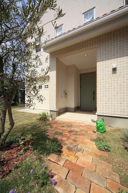 BLUEHOUSE(ブルーハウス)【デザイン住宅、建築家、ガレージ】シンボルツリーやレンガ敷きのアプローチと調和した白い外観。玄関の横にご主人の念願のガレージがある